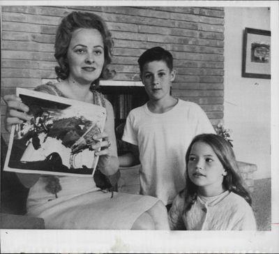 1965 Edward White wife Pat displays photo of husband walk space Press…