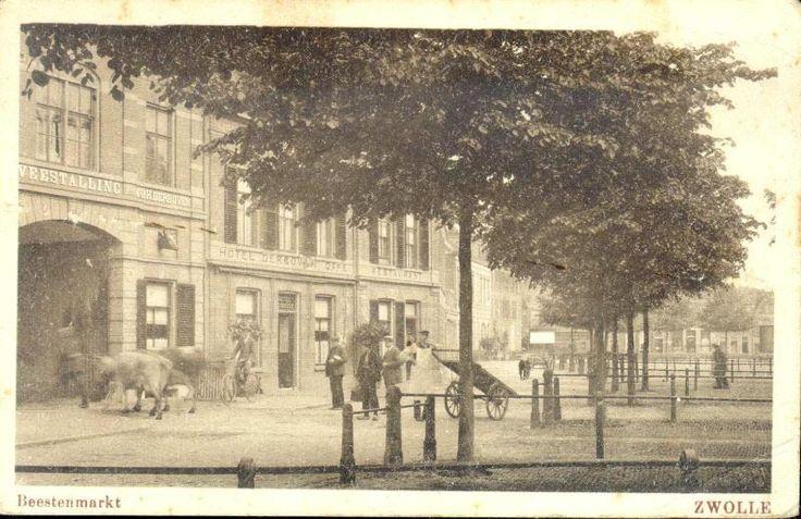 Gezicht op de panden Harm Smeengekade 15 en 16 en op de vee- of beestenmarkt, 1900. Twee koeien worden het pand van de Overijsselsche Veestalling Maatschappij binnengeleid. Een man op een fiets kijkt toe evenals enkele andere heren. Een man met witte schort leunt tegen een handkar. In het pand Harm Smeengekade 15 was van 1900 tot 1931 het hotel-cafe van Derboven gevestigd.