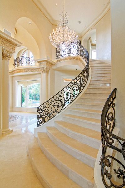 Marble floors, granite columns and walls of windows complement the elegance of the custom staircase.