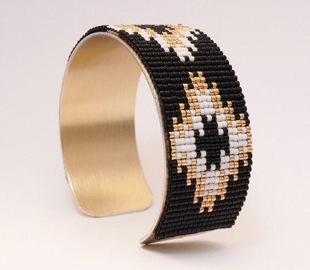 Bracelet manchette en perles Miyuki delicas tissées coloris noir, blanc et doré  Le tissage mesure 25 mm de large et est collé sur un support en laiton qui se règle à la tai - 17268459