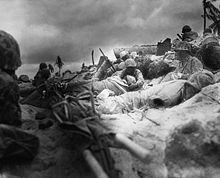 Marines seek cover amongst the dead and wounded behind the sea wall on Red Beach 3, Tarawa
