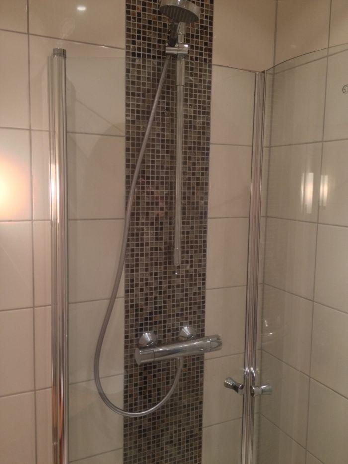 Lyst oppusset #dusj med mosaikkfliser og glassdører.