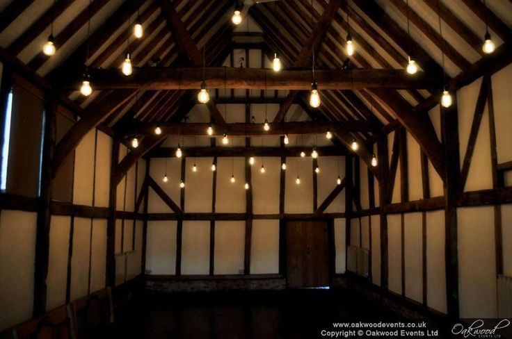 Edison bulbs hung in lines under the beams at Loseley Park. Stylish wedding lighting by Oakwood Events
