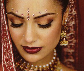 pretty makeup and bindis for desi bride in red