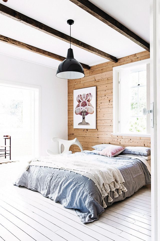 Swedish bedroom with exposed ceiling beams, an industrial pendant light, wood walls, and a low-laying bed