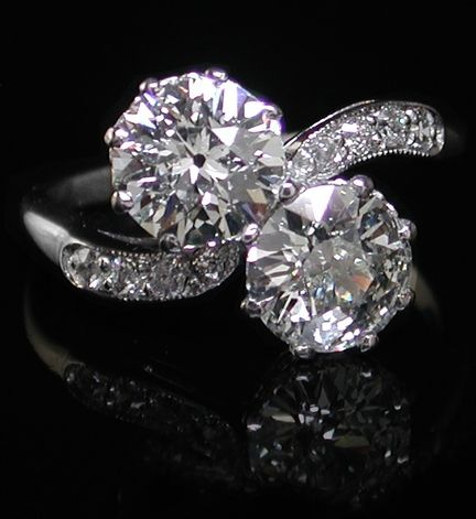 1920'S DIAMOND RING A superb two stone diamond ring from the 1920's. The Old European brilliant cut diamonds are each over 1.00ct in weight, total carat weight 2.14ct. Quality grade estimated as I/SI. The curving cross-over shoulders are inset with small vintage diamonds and the original settings and shank are entirely in Platinum.