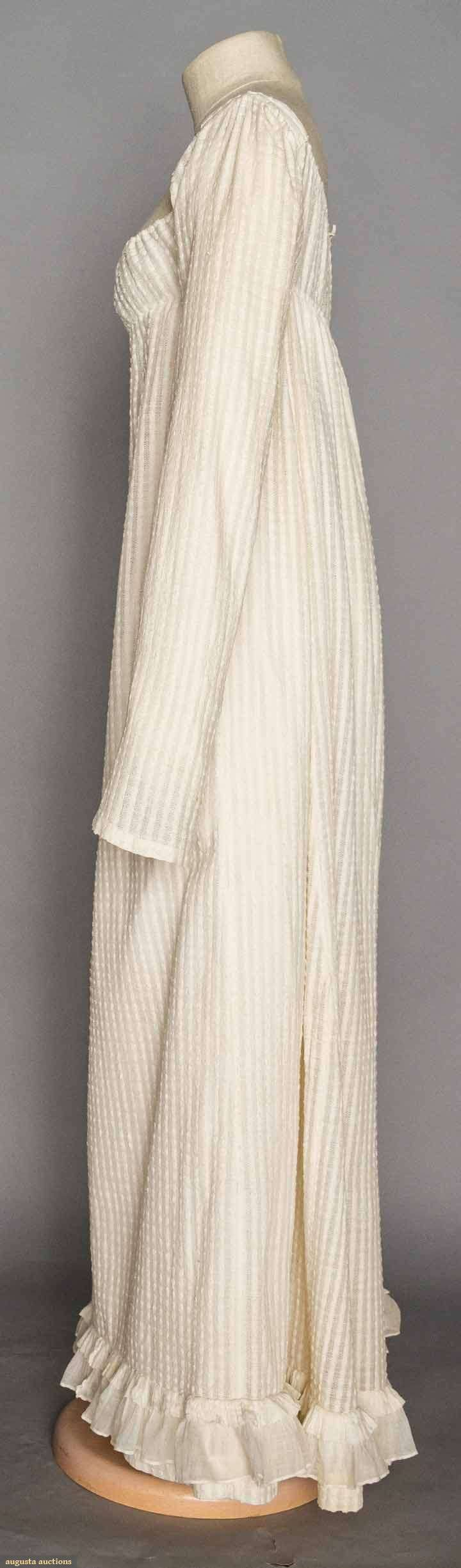 "WHITE COTTON DAY DRESS, 1800-1810 Lot: 8 November 11, 2015 NYC New York City Raised dot textured & striped woven fabric, very high empire bodice, square F neckline, 2 draw-string CB ties, long sleeves, very fine cotton mull double ruffle at hem edge, L 51"", (minor stains, very small holes & 2 mends on bottom F) very good."