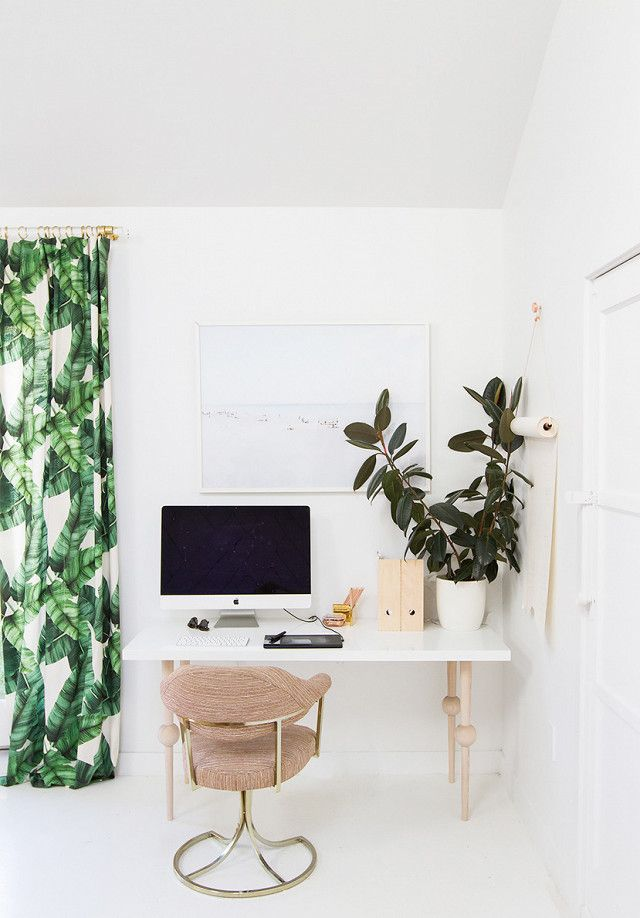 Home office with tropical printed curtains, a customized IKEA desk, and a large plant