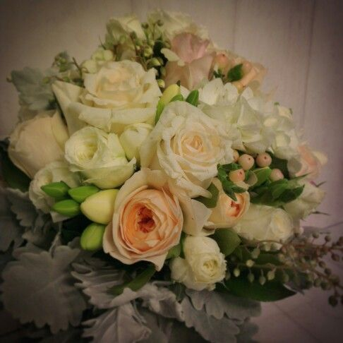 Bridal bouquet made by The Bloom Room of Mornington. Bouquet consisting of roses, David Austin roses freesias, hypericum berry, clethra, dusty miller foliage.