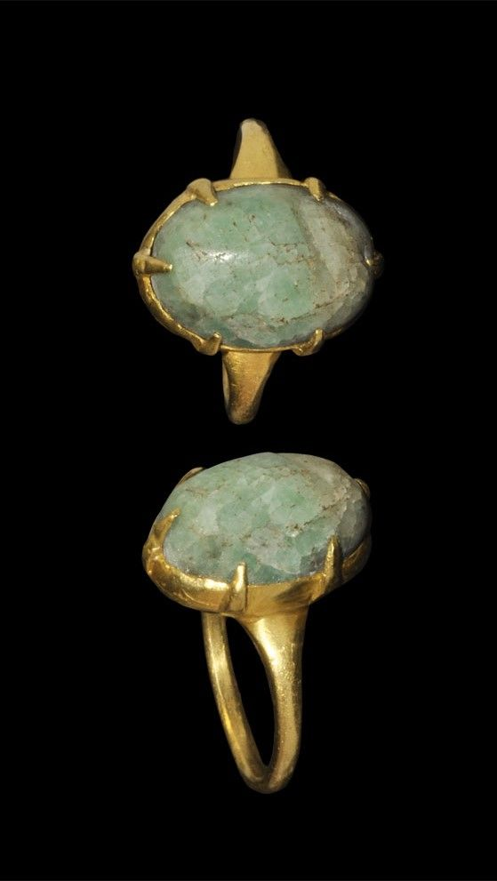 MEDIEVAL GOLD AND EMERALD FINGER RING Circa 13th-14th century AD. A gold finger ring comprising a D-section hoop with expanding shoulders; the bezel a dished claw setting for an elliptical emerald. Gold and gemstone