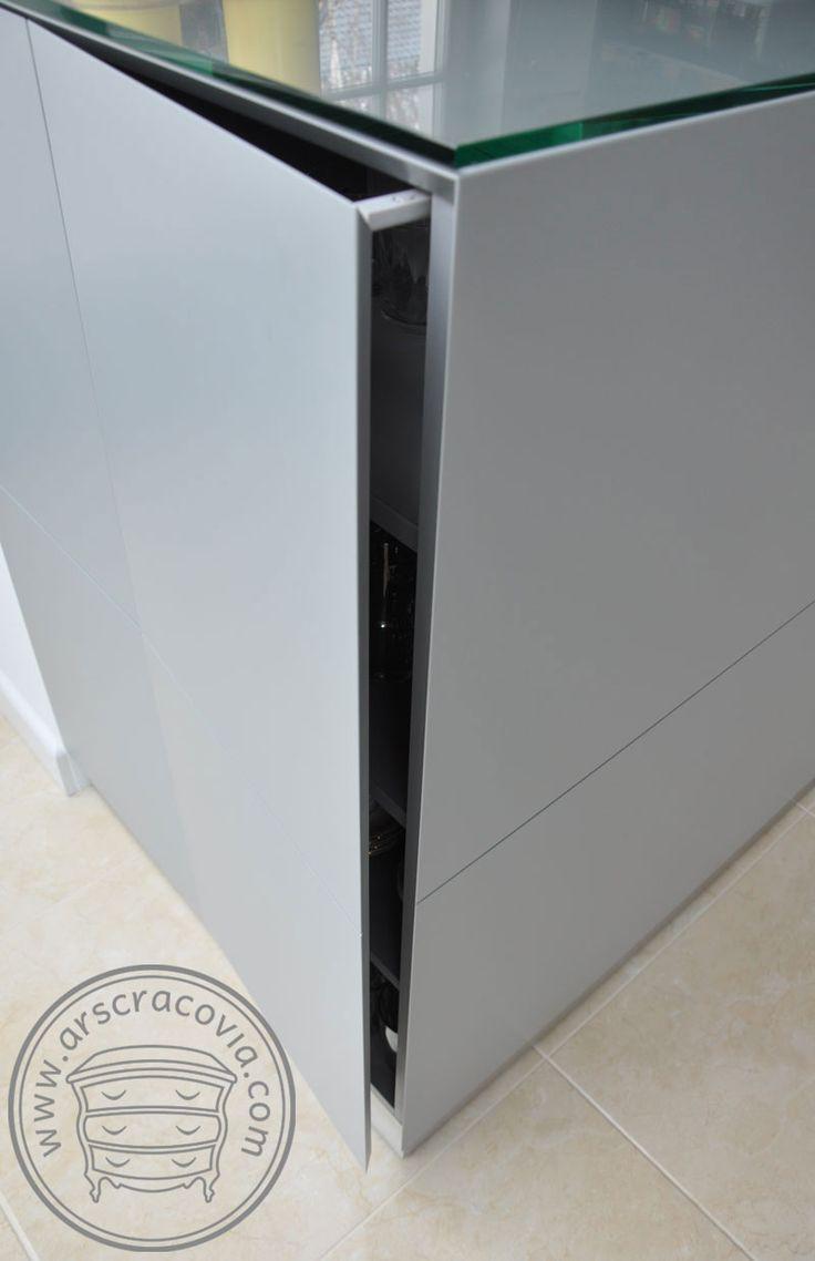 Na krótkim boku lady kuchennej ukryta szafka otwierana od strony jadalni, za pomocą mechanizmu tip-on.
