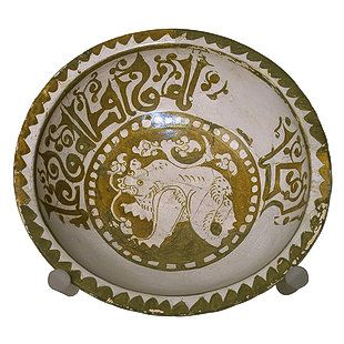 """Coupe avec un rhinocéros, lustre, fatimide, 11è siècle H=8 cm D=27 cm, Inscription en coufique """"et sa gentillesse""""."""