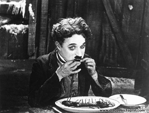 Charlie Chaplin eating his boot in the by now famous scene from The Gold Rush.