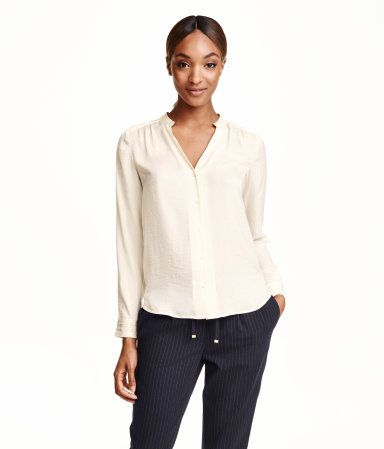 Blouse in softly draping, woven satin fabric. V-neck, buttons at front, and long sleeves with decorative pintucks at cuffs.