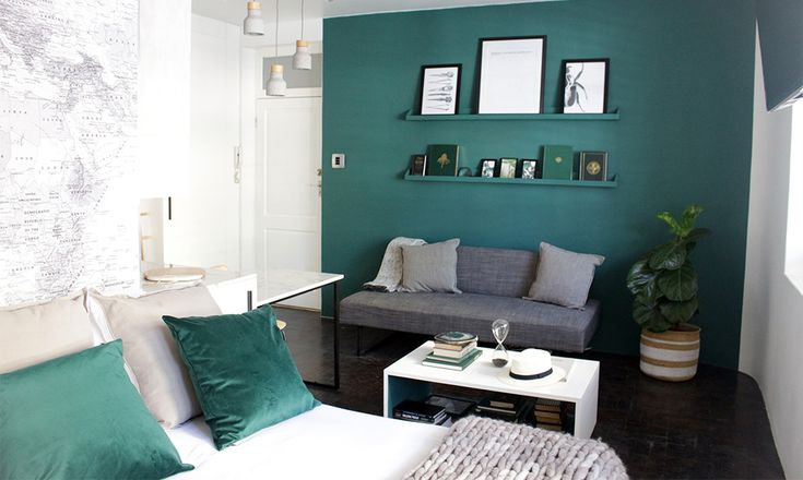 The emerald green of the feature wall is picked up in emerald Touch velveteen cushions from Hertex on the bed and a moss agate on the coffee table. The sofa was custom-made by Sofas and Chairs in Kensington. Draped over the backrest is a graphite-coloured mélange throw from Hertex.