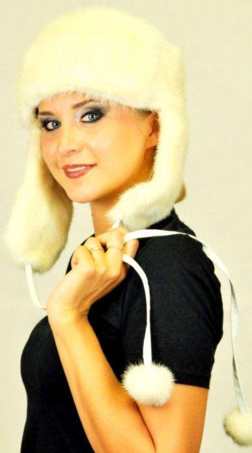 Cappello in visone bianco-crema naturale, con paraorecchie ed originali pom poms in visone. Solo su www.amifur.it
