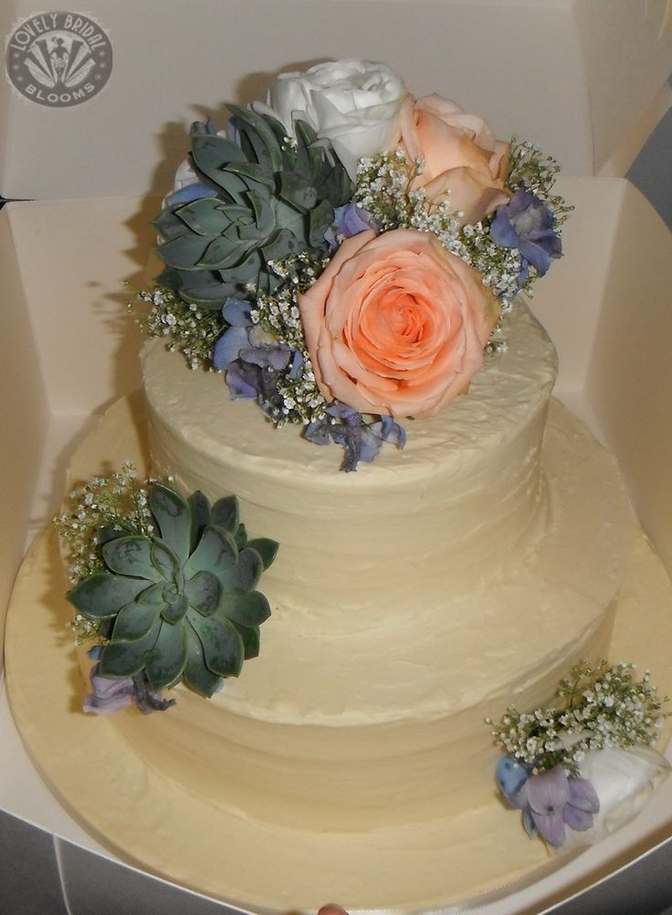 cake topper of fresh succulents, roses ranunculus, delphiniums and babies breath