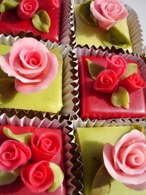 Little square cakes coated in a mix of red and green fondant icing with marzipan roses, rosebuds and leaves. Gorgeous.