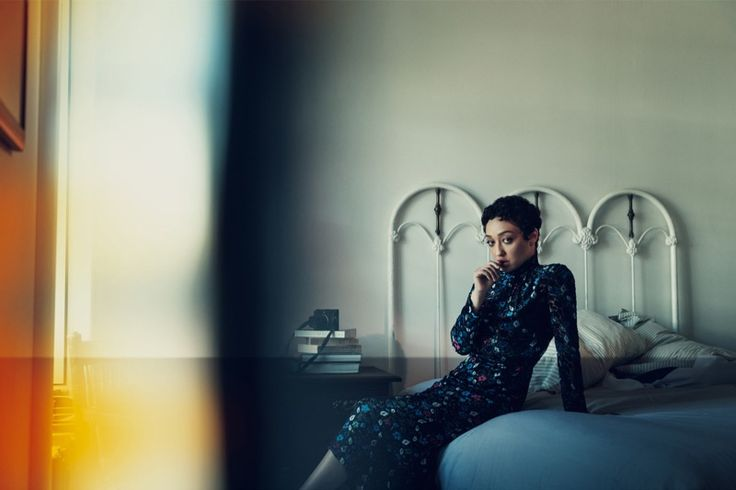 Posing in bed, Ruth Negga wears Prada dress