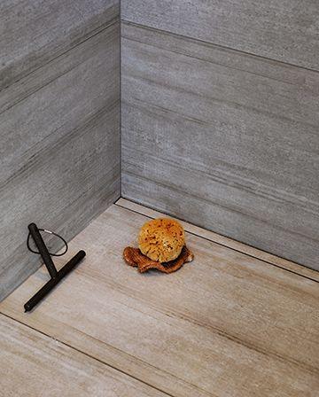 Det skandinaviske badeværelse handler om detaljerne. Her er det familiens afløbsløsning fra Unidrain, der skjules elegant og går i et med fliserne i badet.