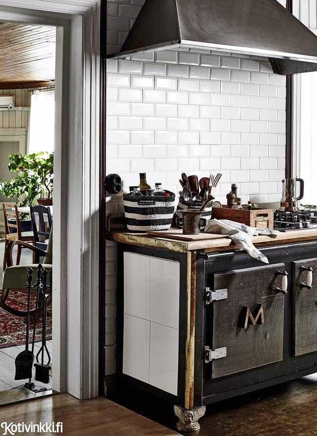 Koti vanhassa kaupassa. Hellan runkona on yliopiston fysiikan laitoksen vanha pöytä. Ajaton metrolaatoitus sopii persoonalliseen keittiöön.