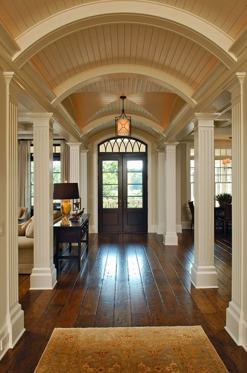 Imposing formal entry hall effect created with Grecian columns and vaulted arched ceilings lined with beadboard. Contrast between dark wood floor and white ceiling plays up the drama!