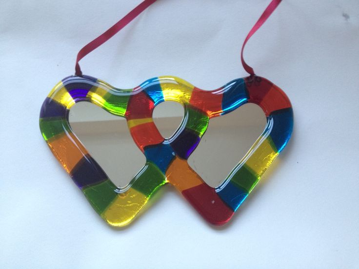 This piece features a multicoloured, fused-glass frame in the shape of two entwined hearts around a mirror. The piece measures approx 22cms wide by 14 cms tall and comes with a hanging ribbon in orange. It is a unique, one-off piece, made by me in my glass studio in England. £36 + p+p
