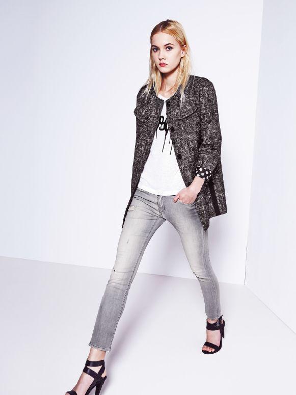 Melanżowy płaszczyk z mankietem w groszki, biała lniana bluzka z czarnym napisem i dopasowane, szare jeansy.