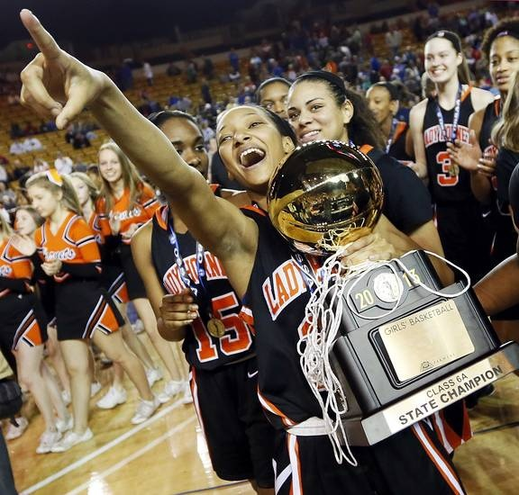 Booker T. Washington's Kaylan Mayberry (12) points to the Hornet fans as she holds the gold ball after the Class 6A girls championship high school basketball game in the state tournament at the Mabee Center in Tulsa, Okla., Saturday, March 9, 2013. Booker T. Washington beat Bixby, 52-46. Photo by Nate Billings, The Oklahoman