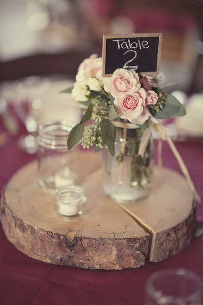 Wooden slabs with votive candles, mini chalkboard table numbers and mason jars of pink garden roses. An effortless rustic chic centerpiece! {Alexis Stein Photography}