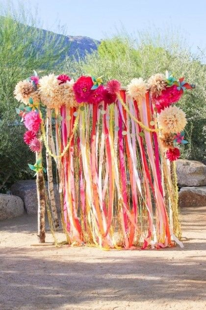 Are you anxious to create an extra special corner at your next outdoor barbecue? Drape lengths of streamers from a simple archway and top with paper flowers and garland.