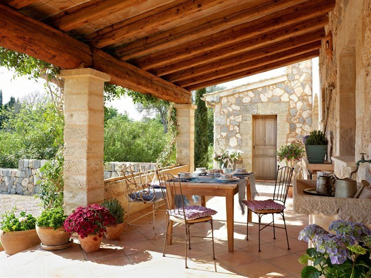 Rustic, angled ceiling with beams, stone patio, stone pillars, wall of windows