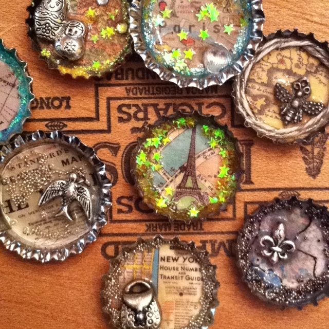 Bottle cap art using charms and vintage maps.