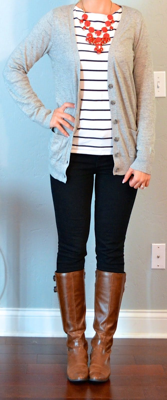 White and black striped shirt, light gray cardigan, jeans, brown riding boots, and red bubble necklace.