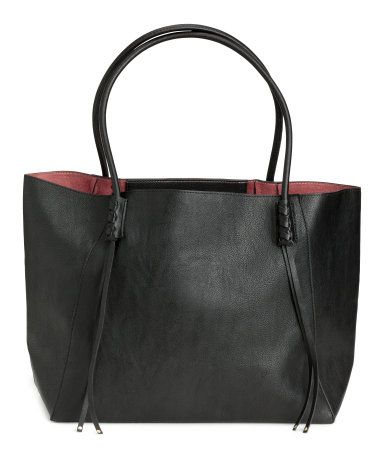 Black. Shopper in imitation leather. Two handles with decorative braiding and fringe details. One inner compartment with zip. Unlined. Size 6 3/4 x 11 1/2 x