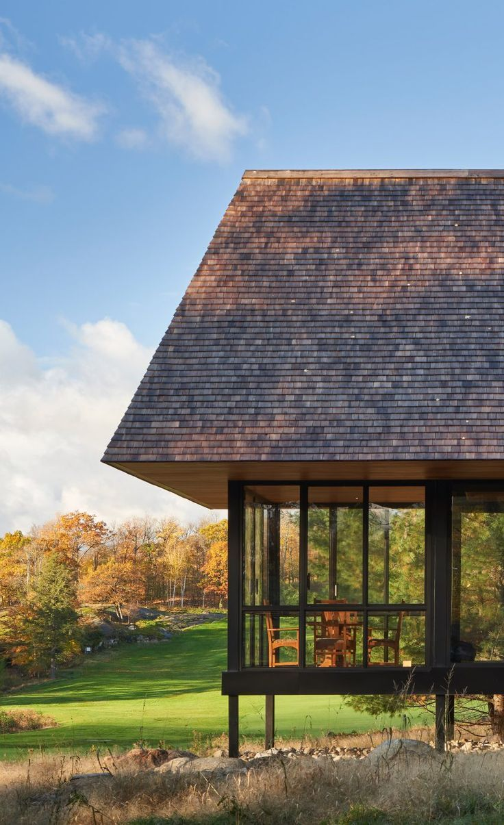 Exterior Walls Are Wrapped In Shiplap Wooden Boards And Large Stretches Of Glass Topping Each Home Is A Large Hip Roof Clad I Hip Roof Architect Architecture