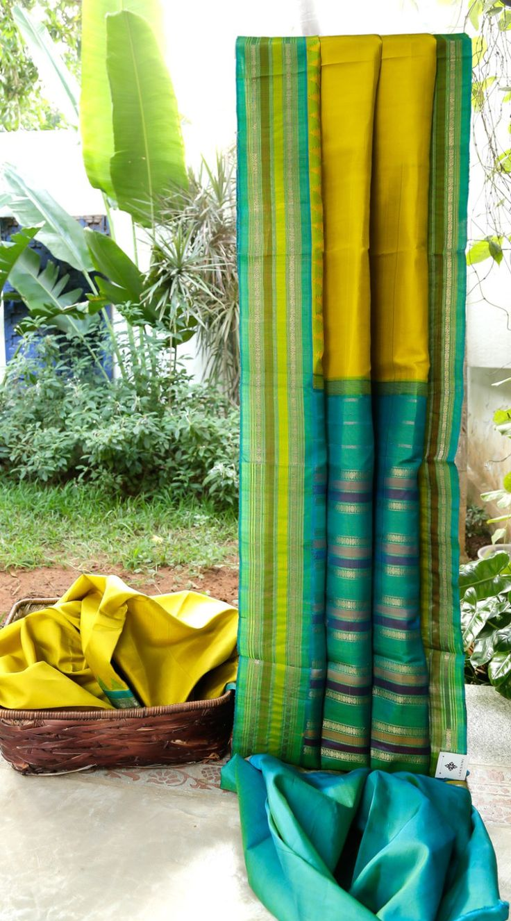This gadwal silk is in a subtle medallion yellow. The border and pallu have bands in cerulean blue, lime green, medallion yellow woven with gold zari making it look simple and delicate