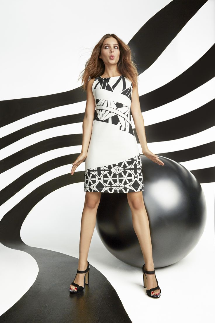 """Say """"Hello"""" to your new favorite dress! This flattering black and white pinafore dress is made of a rigid material which makes it both flattering and the perfect cross-seasonal piece!"""