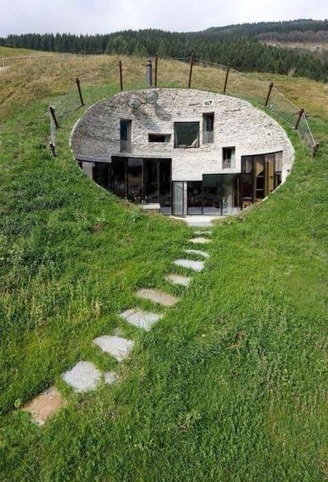 A modern house carved into a hill.