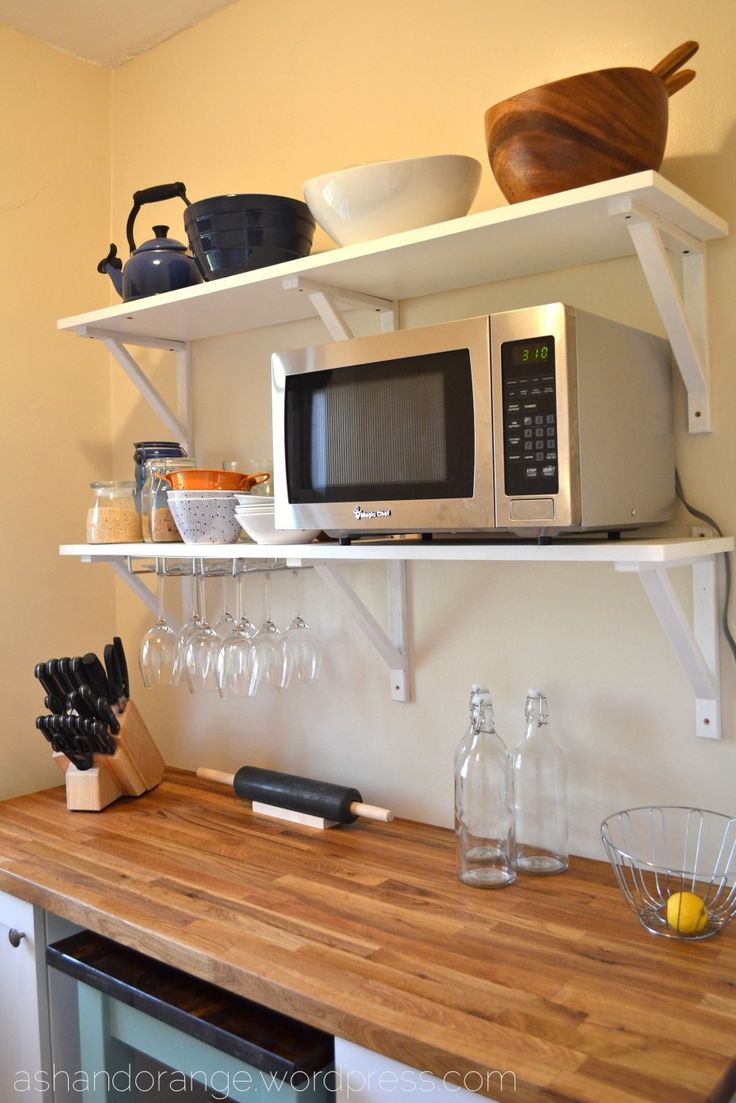 Glass cabinets set in a largely bamboo dominated kitchen - Eye Catching Two Racks Floating Microwave Shelf With Crafts Storage As Well As Smart Glass Holder Attach On White Wall Kitchen Painted And Wooden