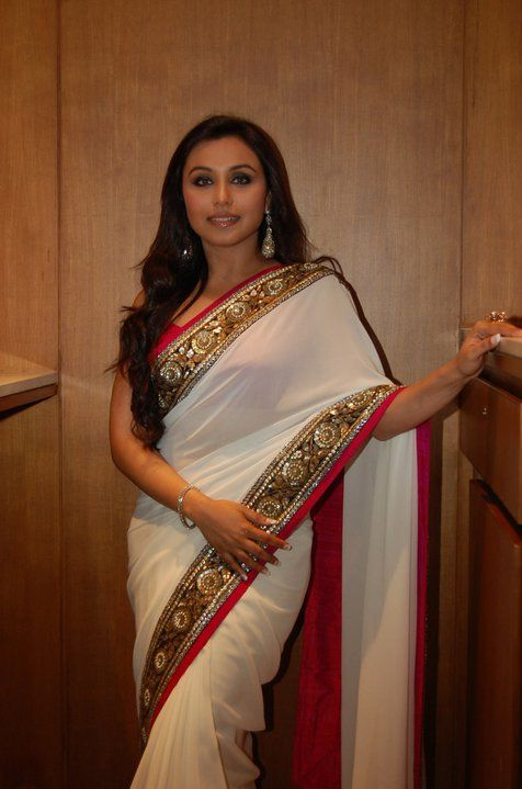 Rani Mukherjee wearing a white saree with a pink and black border with mirror and gold work.