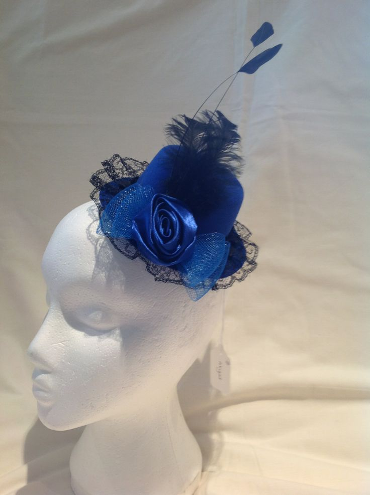 The Abigail is a small fascinator on clips in a sapphire blue top hat shape decorated with black lace edging, a sapphire blue silk rose and crinoline bow finished with black feathers. $70 AUD.