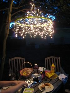 Camping chandelier!  Sm. hula hoop   2 pieces of craft twine cut to 4.5 in  2 strands of icicle lights  fold 2 pieces of twine. tie a loop. You should have 4 single strands.  tie each strand in a knot to the hula hoop.  Wrap the first strand of lights around the hula hoop. repeat