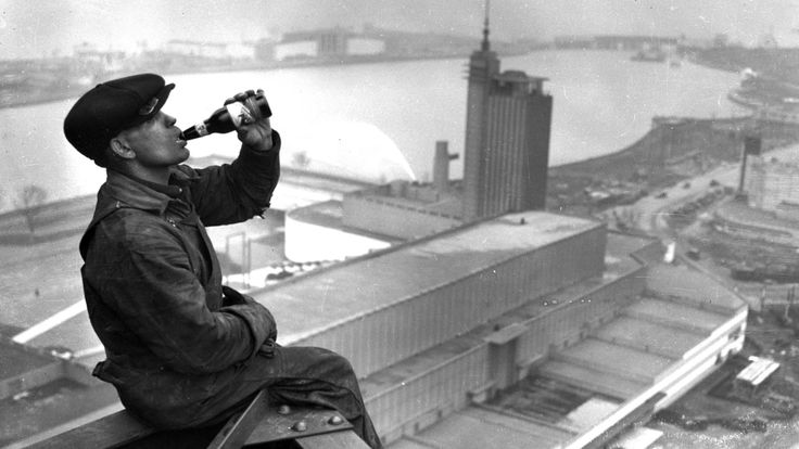 An iron worker perched on the west tower of the Sky Ride drinks an Edelweiss beer during construction of the World's Fair in 1933