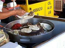 Tacos de suadero (grey) and chorizo (red) being prepared at a taco stand