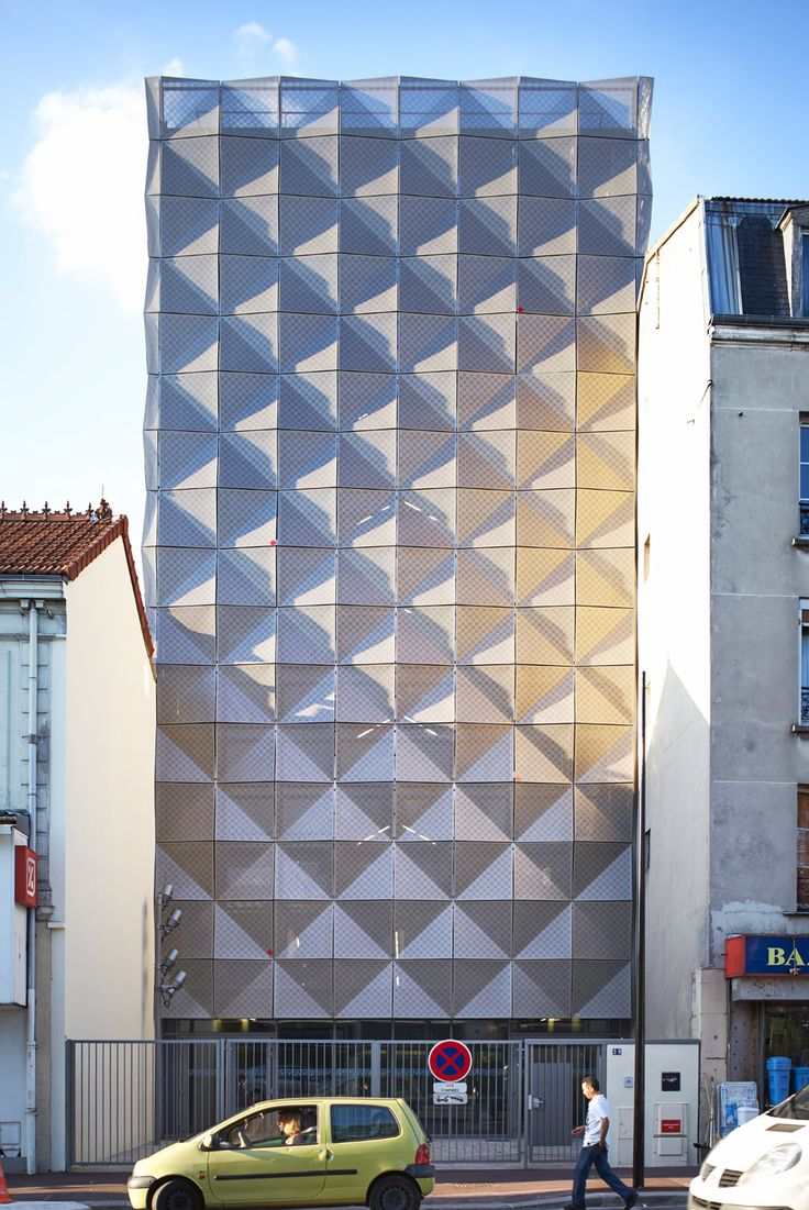 Folded tiles of perforated metal envelop this dance school in Paris by Lankry Architectes, creating a pattern of triangular facets