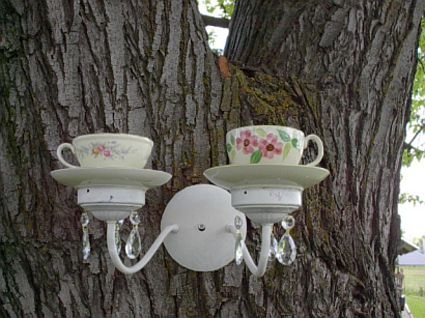 Repurposed tea cups and fixture as bird feeders. Could also use for candles.