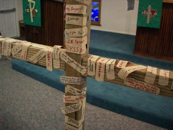 The band-aid prayers on the cross represent our own human brokenness and the presence of God in the midst of suffering.