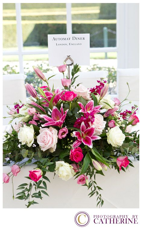 The top table with a long low arrangement in rich pinks