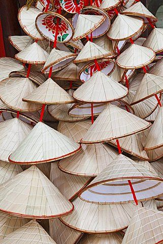 Souvenir conical hats. Hanoi, Vietnam. This style of hat is used as protection from the sun and rain. When made of straw or matting, it can be dipped in water and worn as a cooling protection.